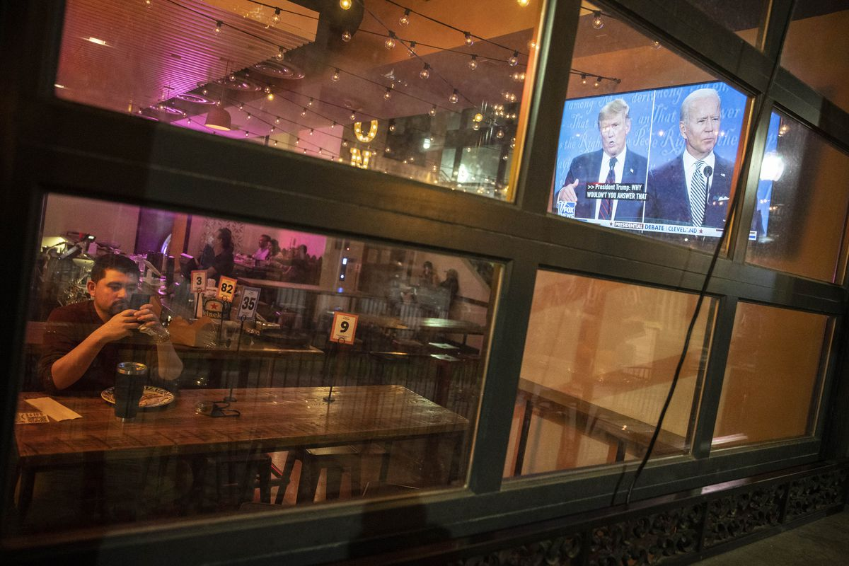 A man sitting in a bar looks at his phone, while on a large TV screen nearby, Trump and Biden debate.