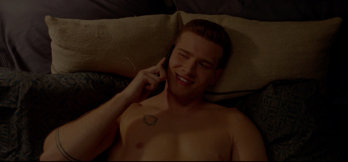 Still of Buck on the phone in bed, smiling