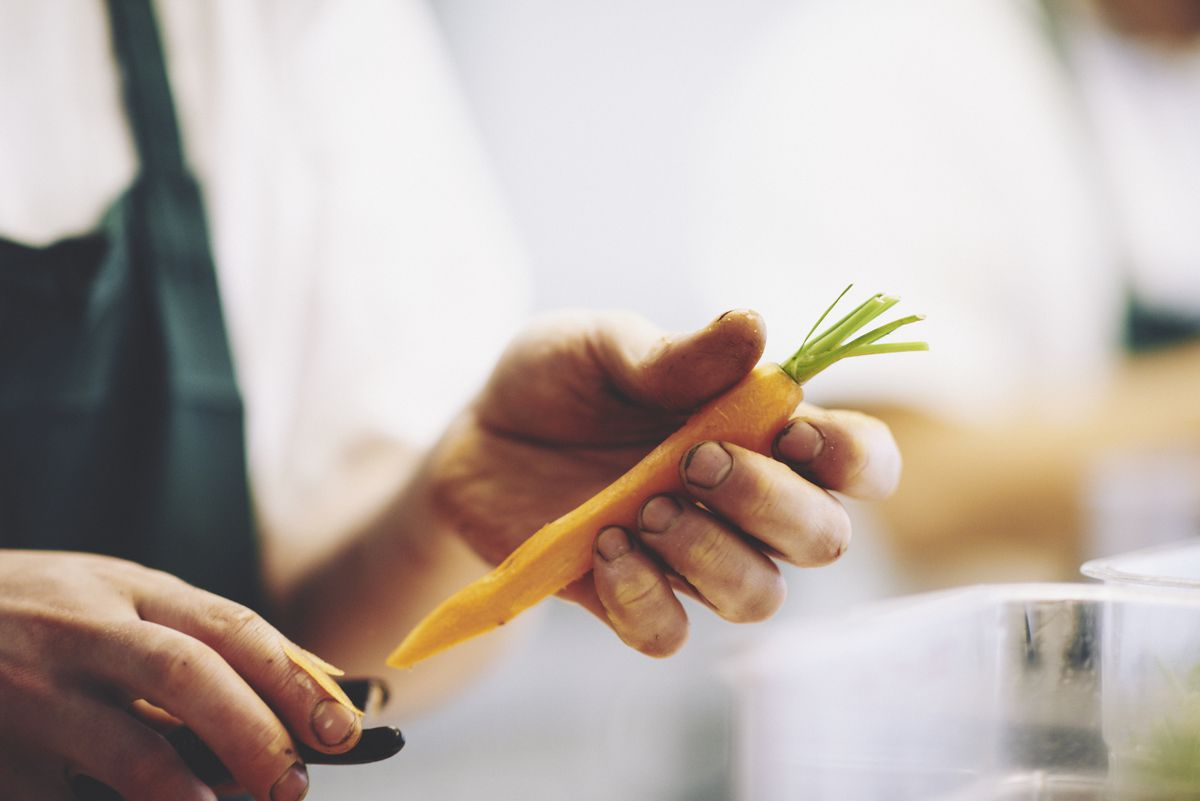 A chef peels a carrot at two Michelin star restaurant Core by Clare Smyth in Notting Hill, London