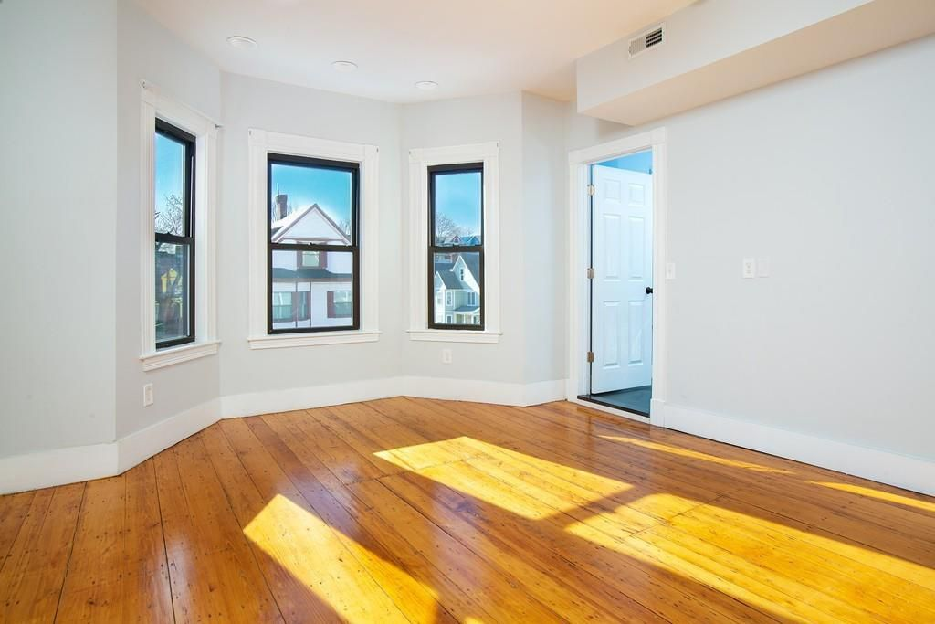 An empty room with a bay window and an open door leading off it.