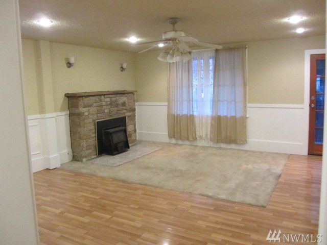 An empty living room with hardwood floors and a brick fireplace