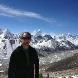 Steve Pearson pauses for a photo on his way up Mount Everest last month. The pointy peak near his head is another famous mountain called Ama Dablam. This photo was taken from Kala Pathar.