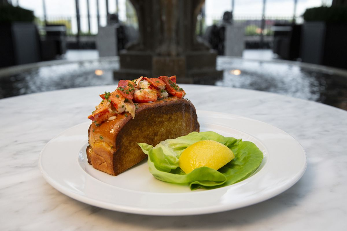 A lobster roll on round plate.