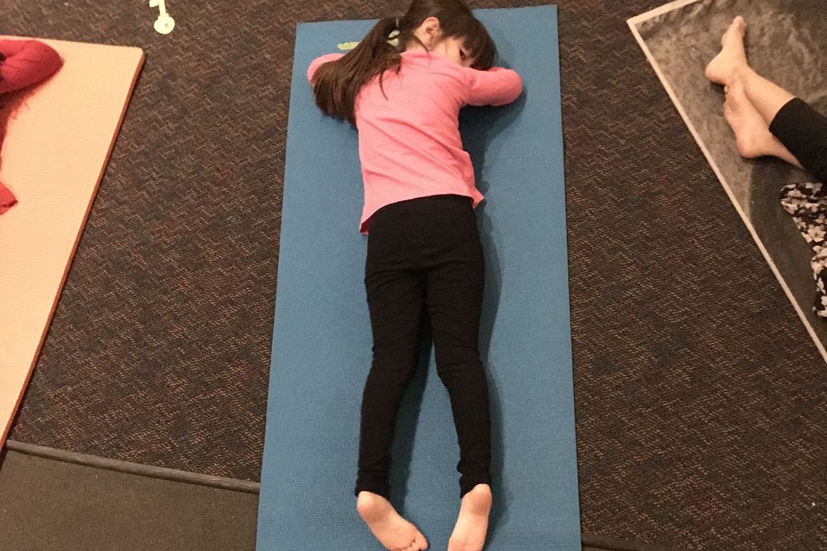 A girl rests at the end of yoga club at Doull Elementary in Denver.