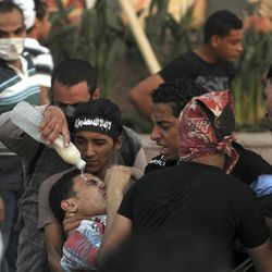Egyptian protesters react from the tear gas during clashes near the U.S. embassy in Cairo, Egypt, Friday, Sept. 14, 2012. Protesters clashed with police near the U.S. Embassy in Cairo for the third day in a row. Egypt's Islamist President Mohammed Morsi vowed to protect foreign embassies in Cairo, where police were using tear gas to disperse protesters at the U.S. mission.