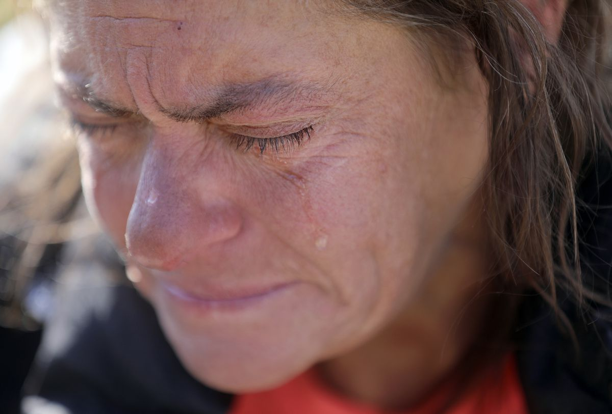 """Stacy Evans cries on while sitting on a sidewalk outside of the Lantern House, a homeless shelter in Ogden, on Tuesday, Oct. 1, 2019. """"We've been through hell. It sucks to be homeless,"""" she says."""