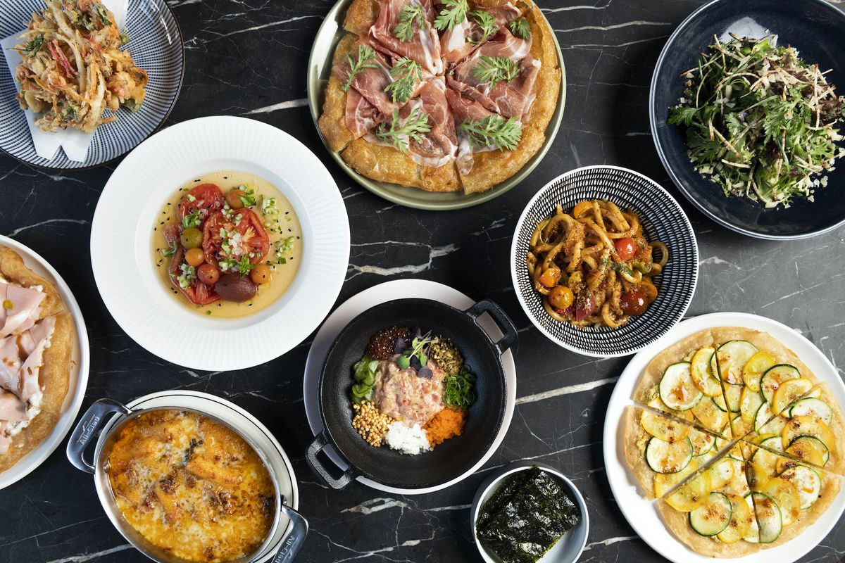 An overhead photograph of several colorful plates, bowls, and metal containers of food from