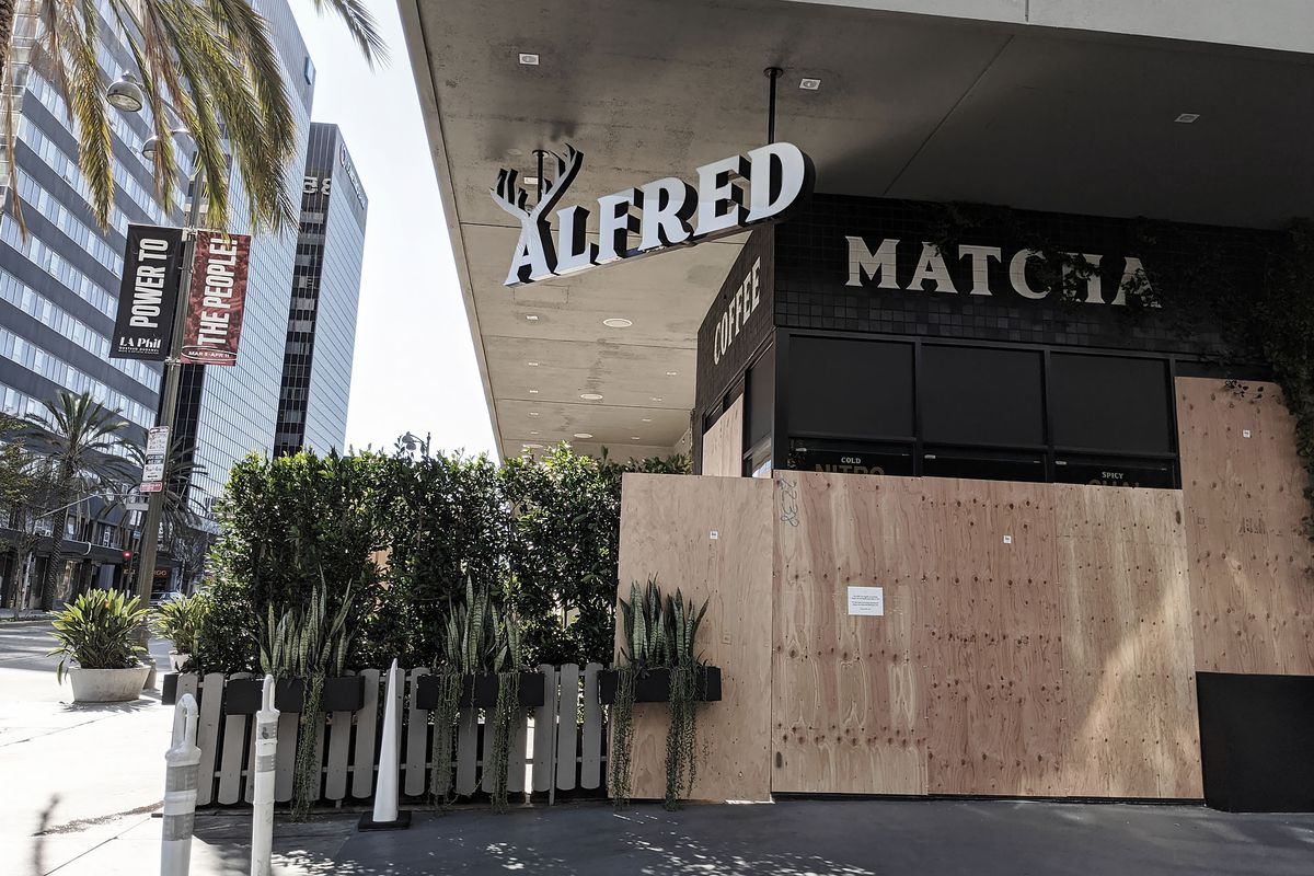 The Line Hotel is boarded up beneath a sign for an Alfred coffee shop.