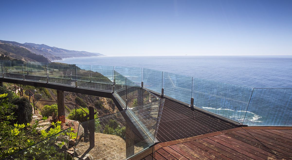 A deck leads to a bridge with glass walls. The ocean sits on the right high above the home.