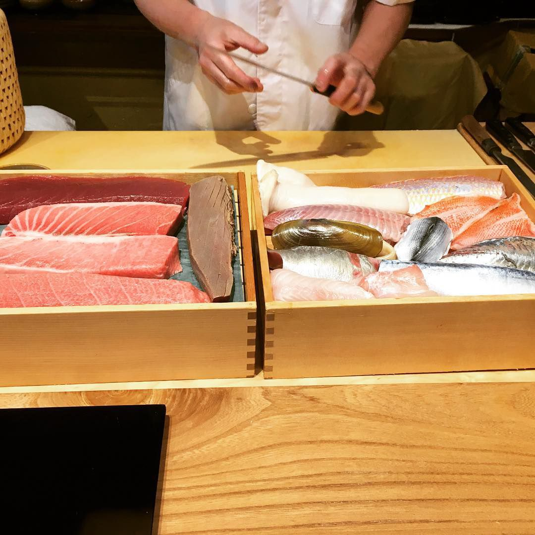 Two wooden boxed filled with raw fish (included salmon and sushi), with a chef in the background holding a knife