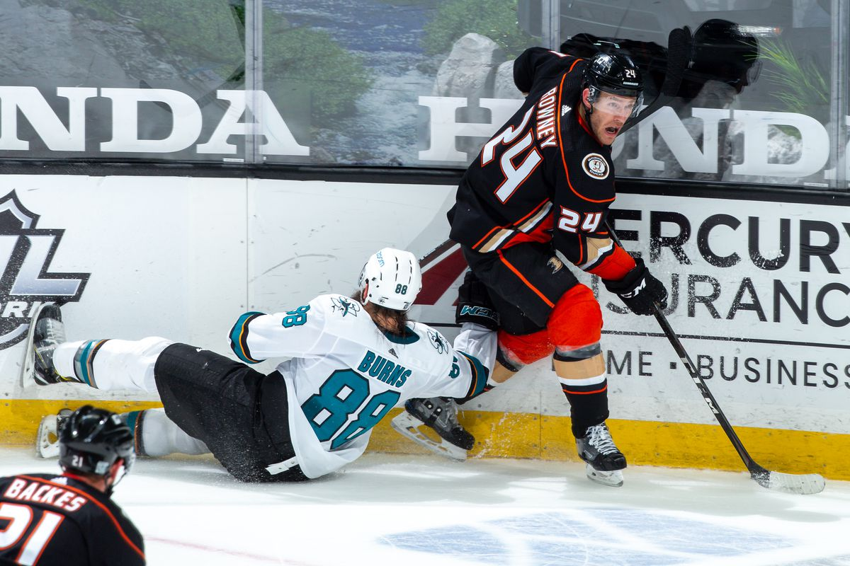 Carter Rowney #24 of the Anaheim Ducks skates with the puck as Brent Burns #88 of the San Jose Sharks falls to the ice during the third period of the game at Honda Center on February 6, 2021 in Anaheim, California.