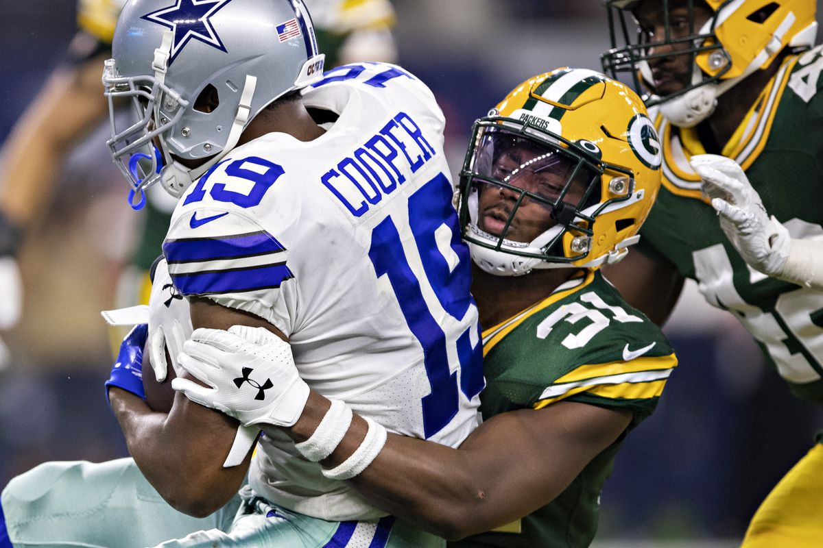 Adrian Amos of the Green Bay Packers tackles Amari Cooper of the Dallas Cowboys at AT&T Stadium on October 6, 2019 in Arlington, Texas.
