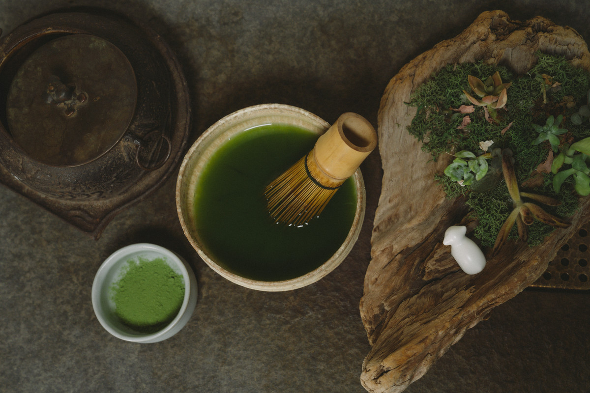 A matcha whisk sits in a bowl of green tea.