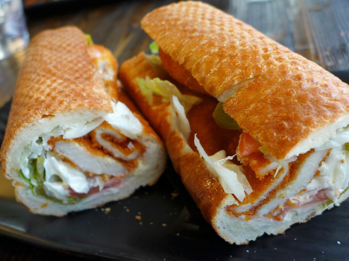 a breaded cutlet hero sandwich cut in half to show cross section.