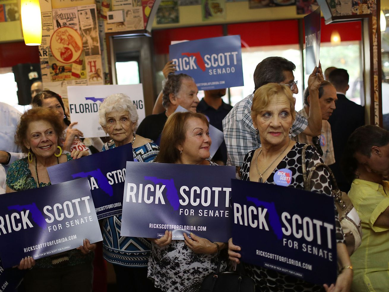 People wait for the arrival of Florida Gov. Rick Scott for a campaign stop at a Cuban restaurant in Hialeah, Florida.