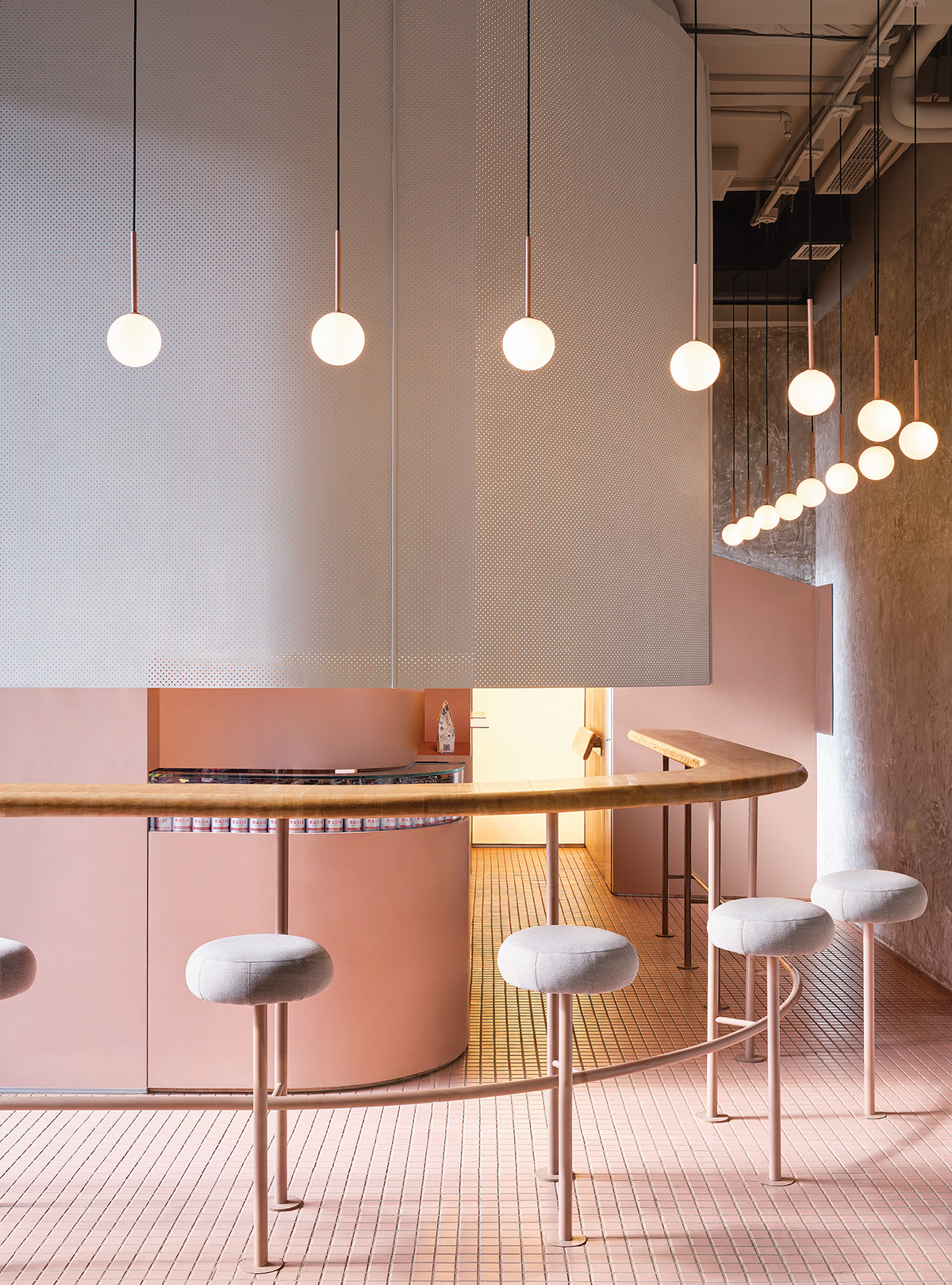 Pink coffee shop with stools and curved coffee bar.