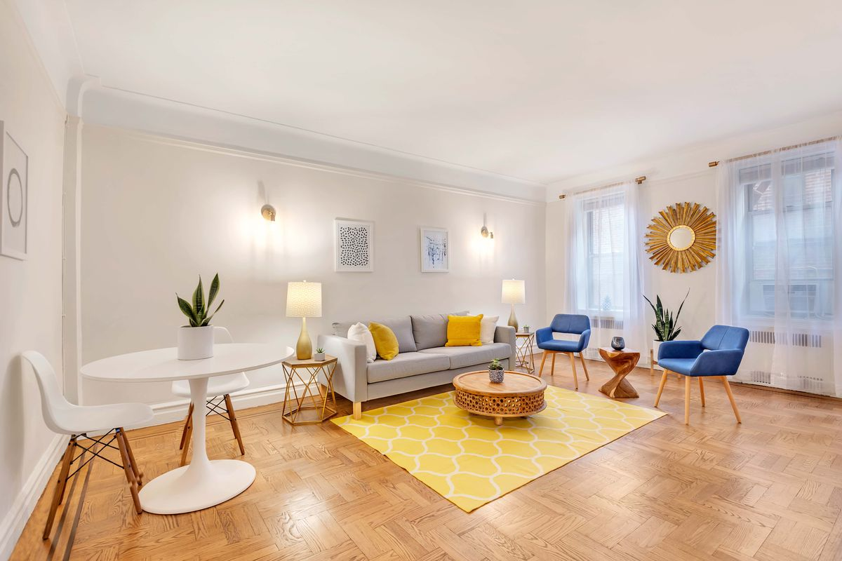 A living area with hardwood floors, a round table, a yellow rug, two blue chairs, and a light grey couch.