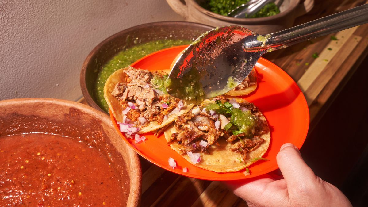 A metal spoon ladles salsa over an orange plate filled with street tacos