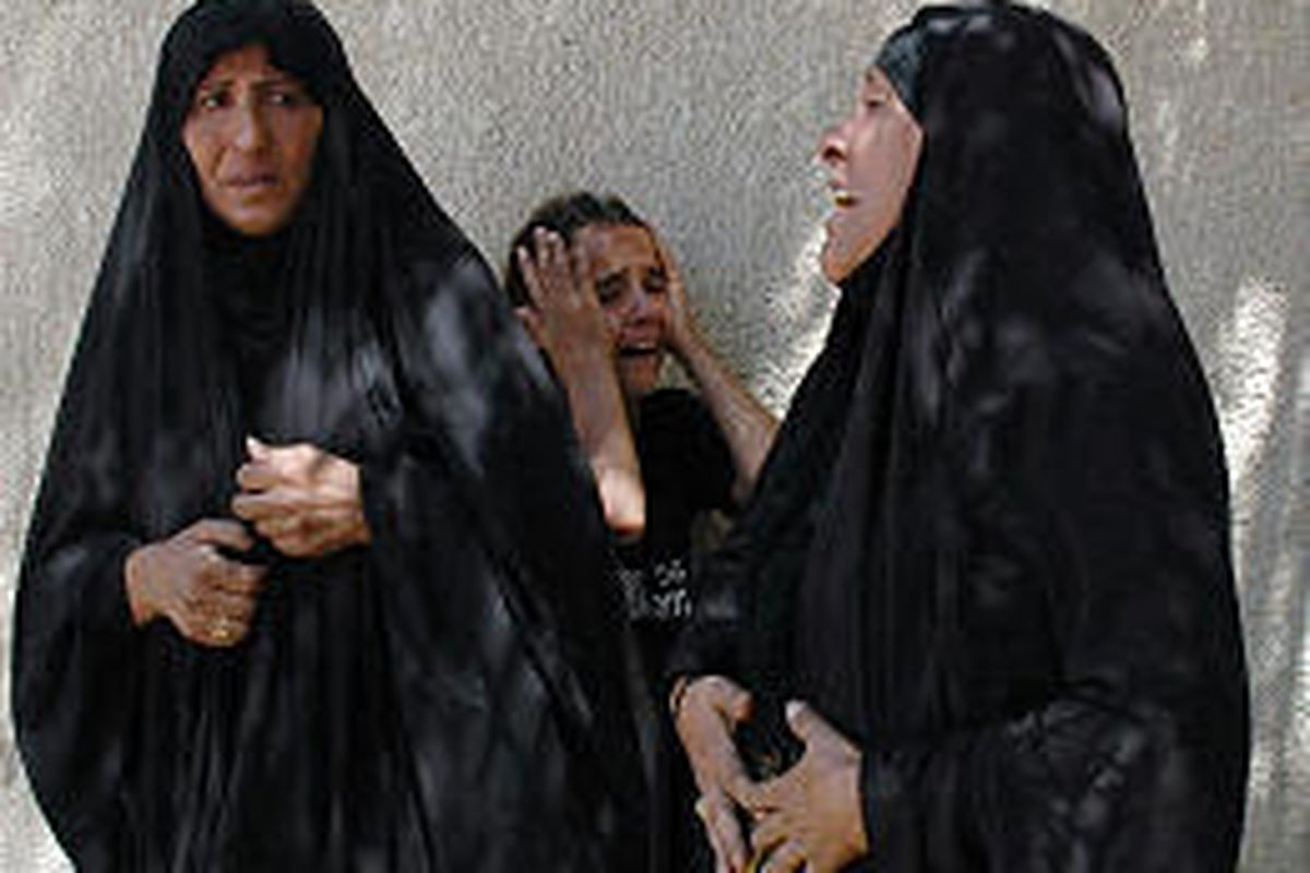 The mother of three Iraqis, right, and their sister wail as the bodies arrive at morgue.