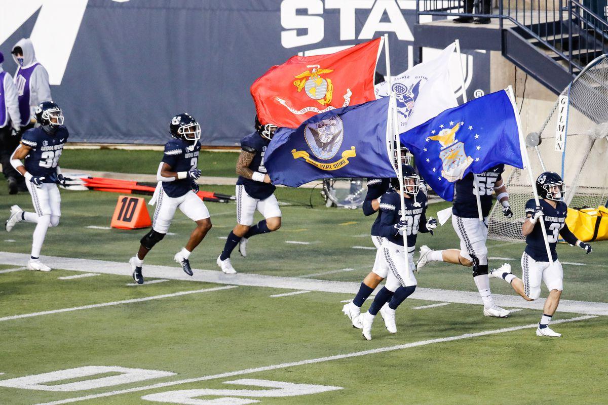 Utah State Aggies football players run onto the field at Maverik Stadium in Logan, Utah.