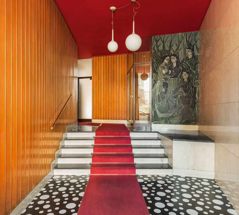 The interior of Via Pinturicchio in Milan. There is a red carpet running up the staircase. The walls are wood. There is a red ceiling.