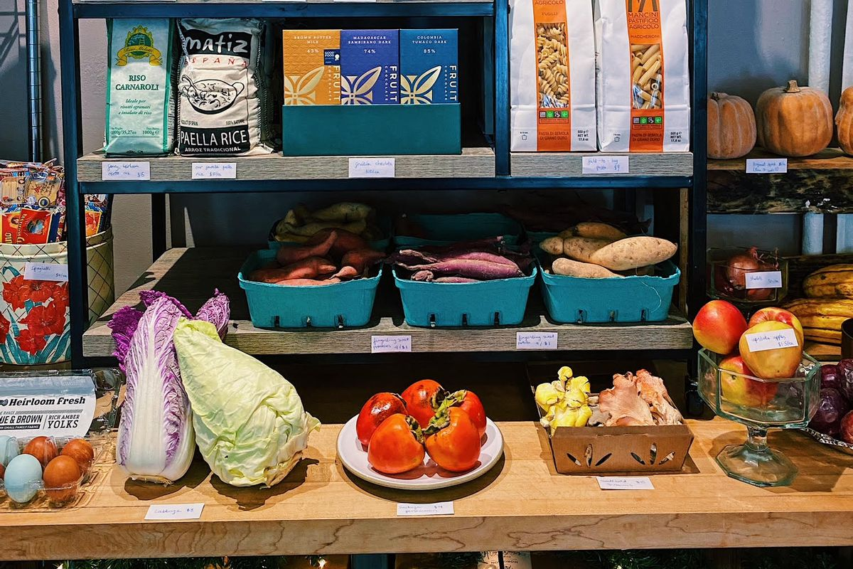 Tomatoes, lettuce, and other produce appear on a wooden table. Stacked high above them on a shelf is a selection of pantry items, including tomato sauce, pasta, and canned condiments.
