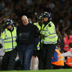 A soccer supporter is led away by British riot police officers during an English League Cup soccer match between West Ham and Millwall, at Upton Park Stadium, London, Tuesday.