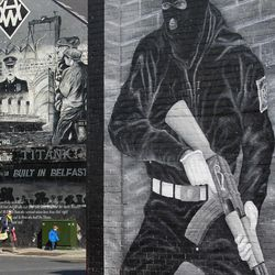 People walk past a Titanic mural  in the Loyalist  Newtownards Road area of East Belfast, Northern Ireland, Friday, April 13, 2012.