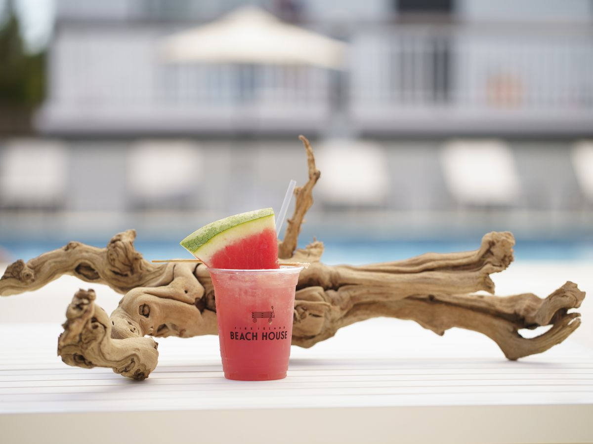 A slushee cocktail in a plastic cup with a watermelon slice sits in front of a driftwood log