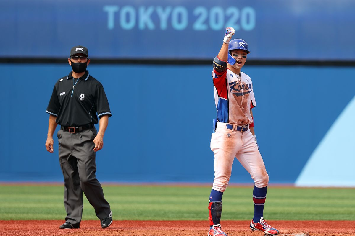 Hae Min Park #17 of Team South Korea celebrates after hitting a two-RBI double to left field in the fifth inning against Team Israel as second base umpire Katsumi Manabe looks on during the knockout stage of men's baseball on day ten of the Tokyo 2020 Olympic Games at Yokohama Baseball Stadium on August 02, 2021 in Yokohama, Kanagawa, Japan.