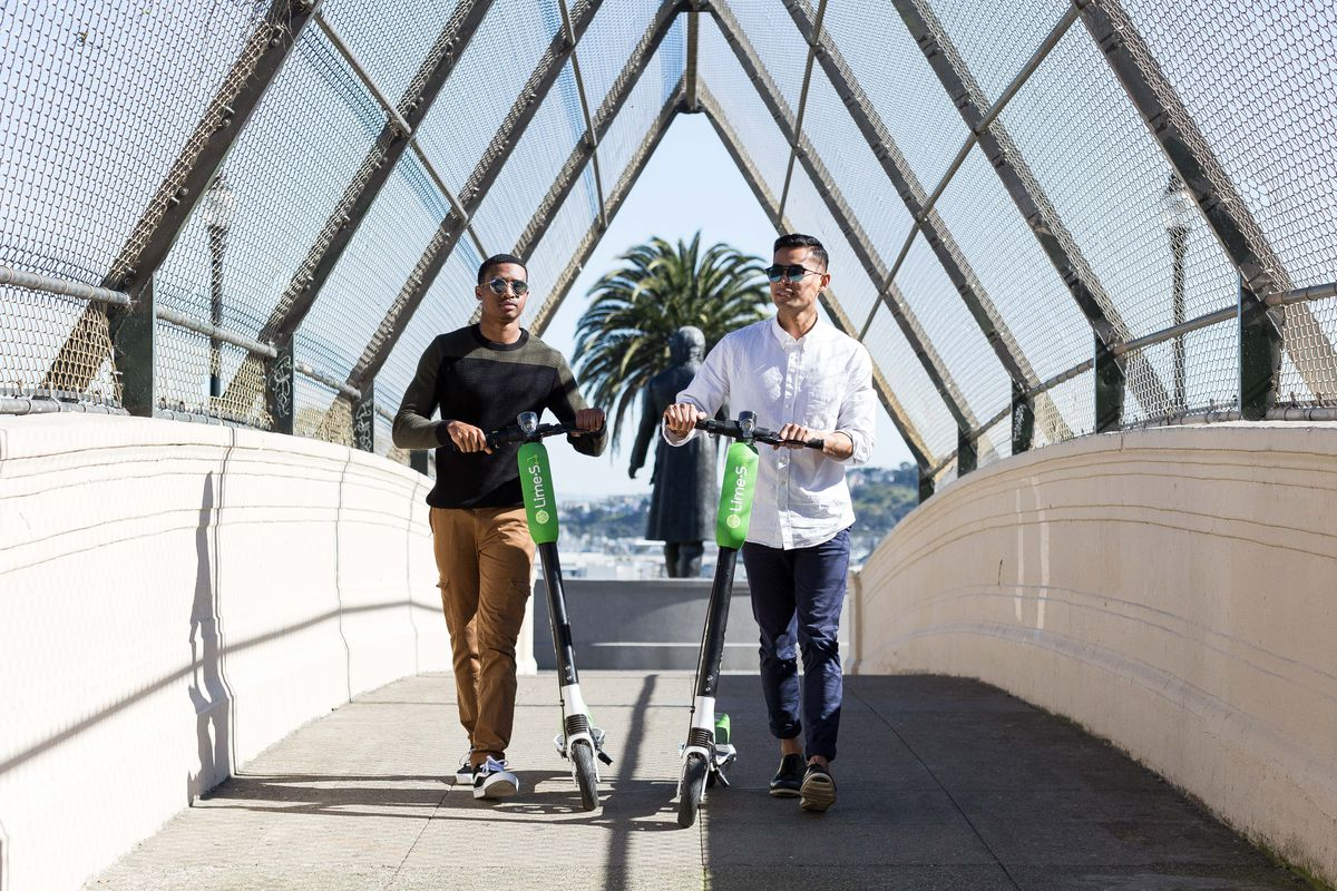 Two people push Limebike scooters over the Dolores Park bridge in San Francisco.