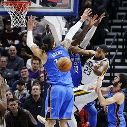 Utah Jazz forward Royce O'Neale passes around Oklahoma City Thunder center Steven Adams and forward Paul George during NBA basketball in Salt Lake City on Saturday, Dec. 23, 2017.