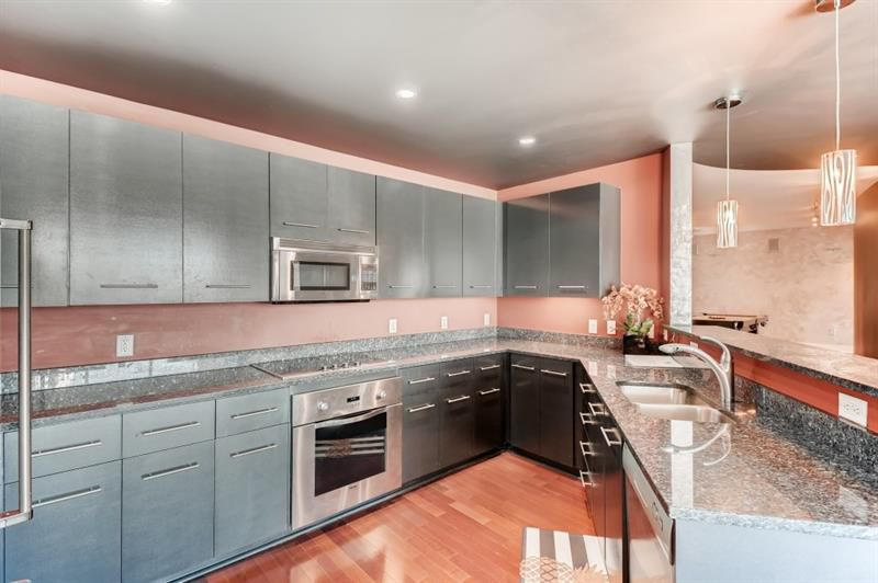 A large black and pink kitchen in a condo in Atlanta.