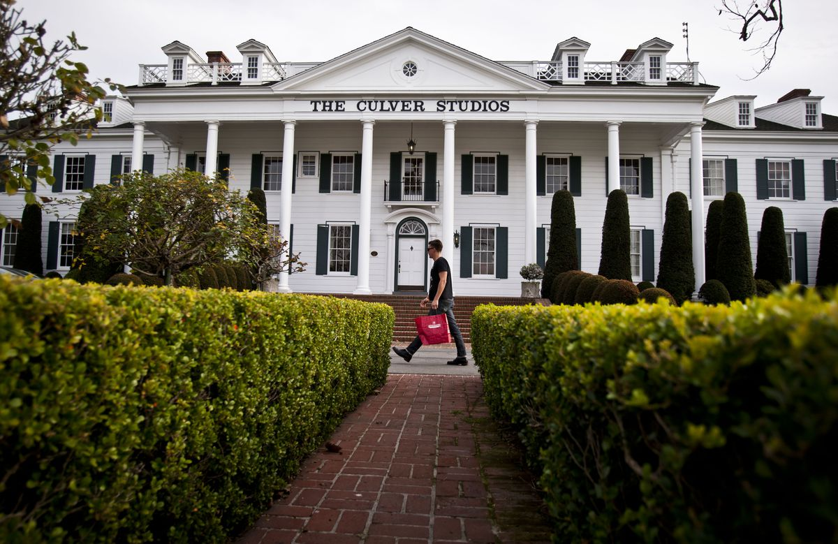 "A color photo of a white Colonial-style mansion fronted my manicured gardens. A man with a red tote bag walks in front of the mansion, which has a simple serif sign that reads ""The Culver Studios."""