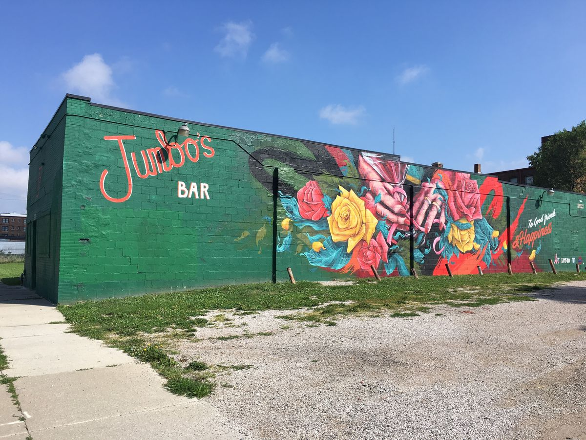 The exterior of Jumbo's Bar on a sunny day. Jumbo's is painted bright green with a mural featuring roses being tied together by a hand with red manicured nails