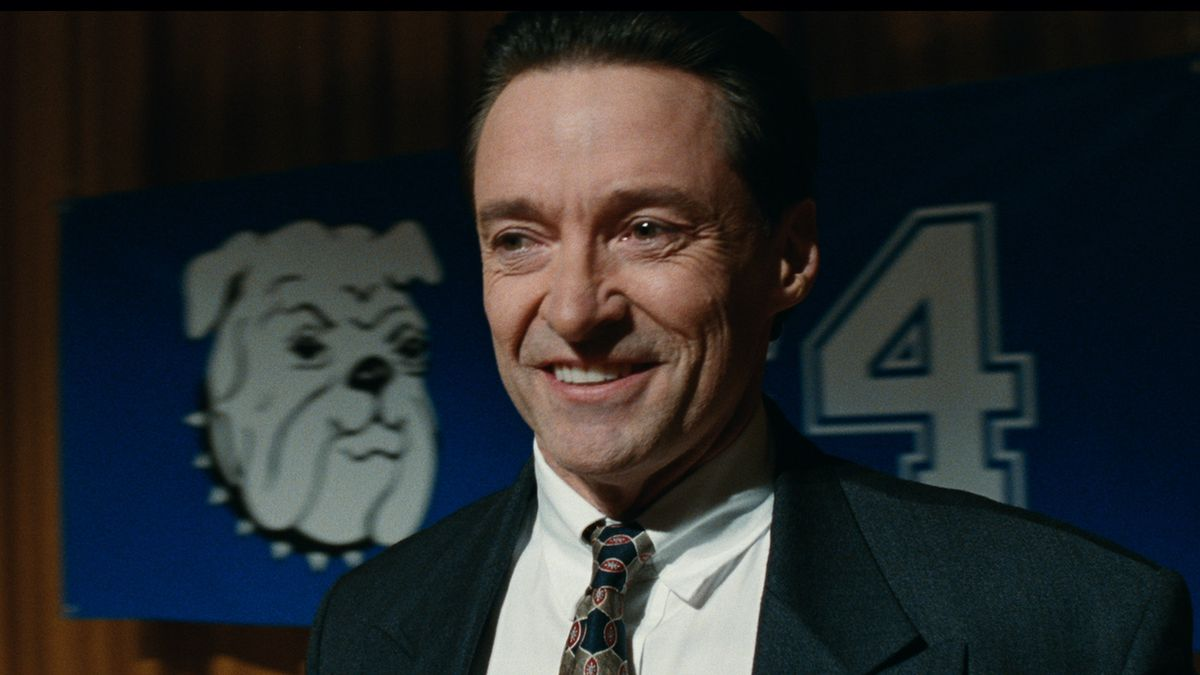 As Long Island school superintendent Frank Tassone, Hugh Jackman smiles broadly while standing in front of a backdrop with the school's bulldog mascot.