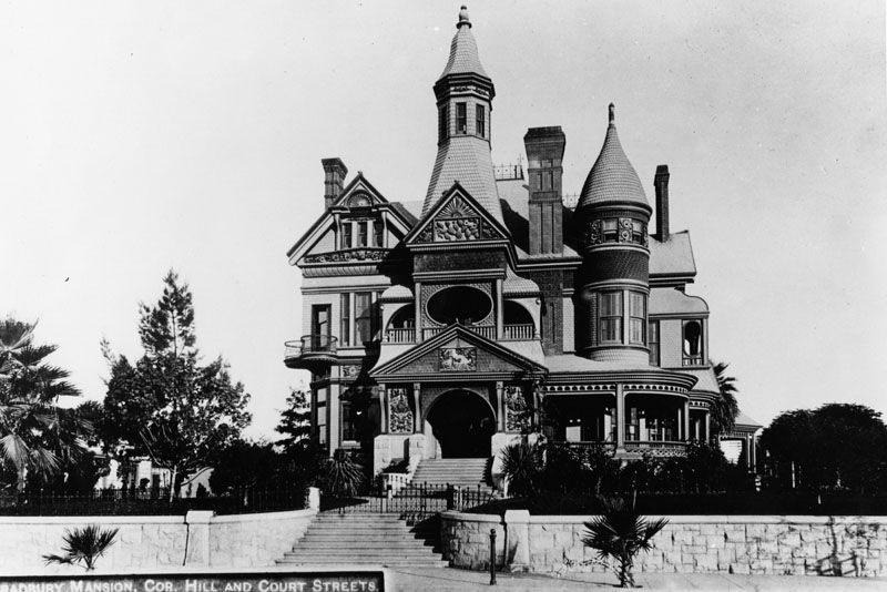 A large mansion with towers. There is a fence in front of the mansion.