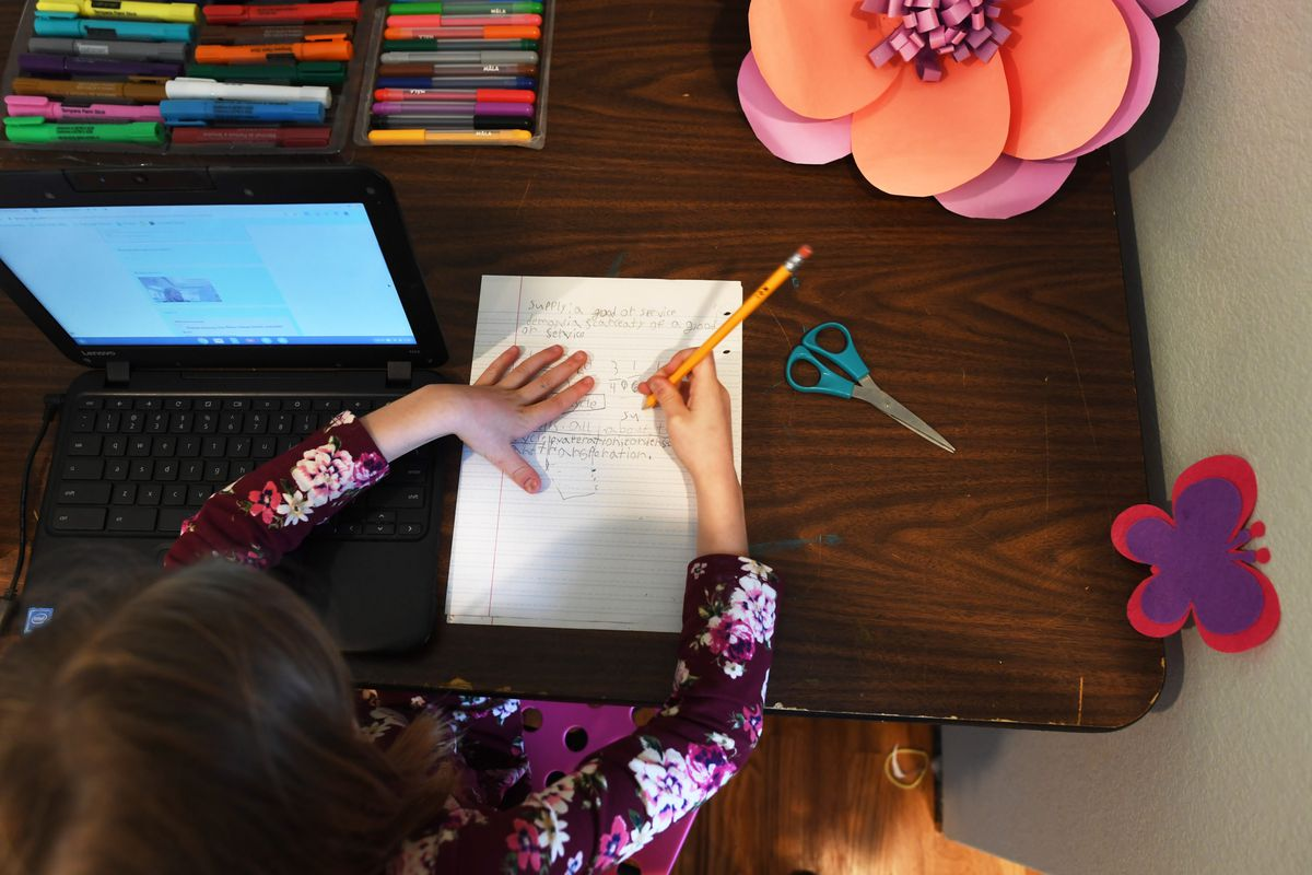 A third-grade student works at home on a computer after her Colorado school closed due to concerns about the new coronavirus.