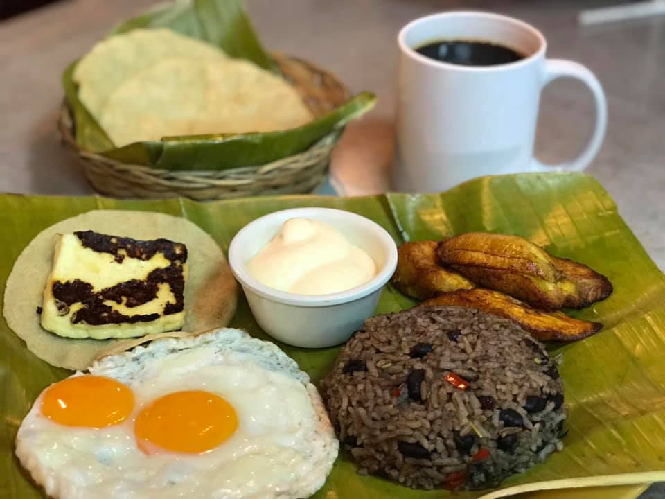 A banana leaf topped with fried eggs, gallo pinto, a cup of sour cream, fried cheese, tortillas, and a cup of coffee