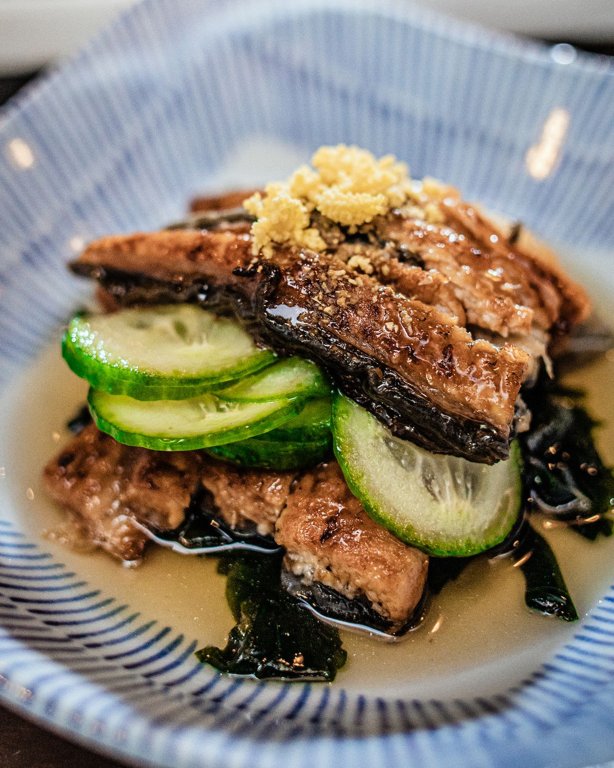 Pieces of browned eel stacked on a plate with a layer of sliced cucumber in between and some crumbled egg yolks on top.
