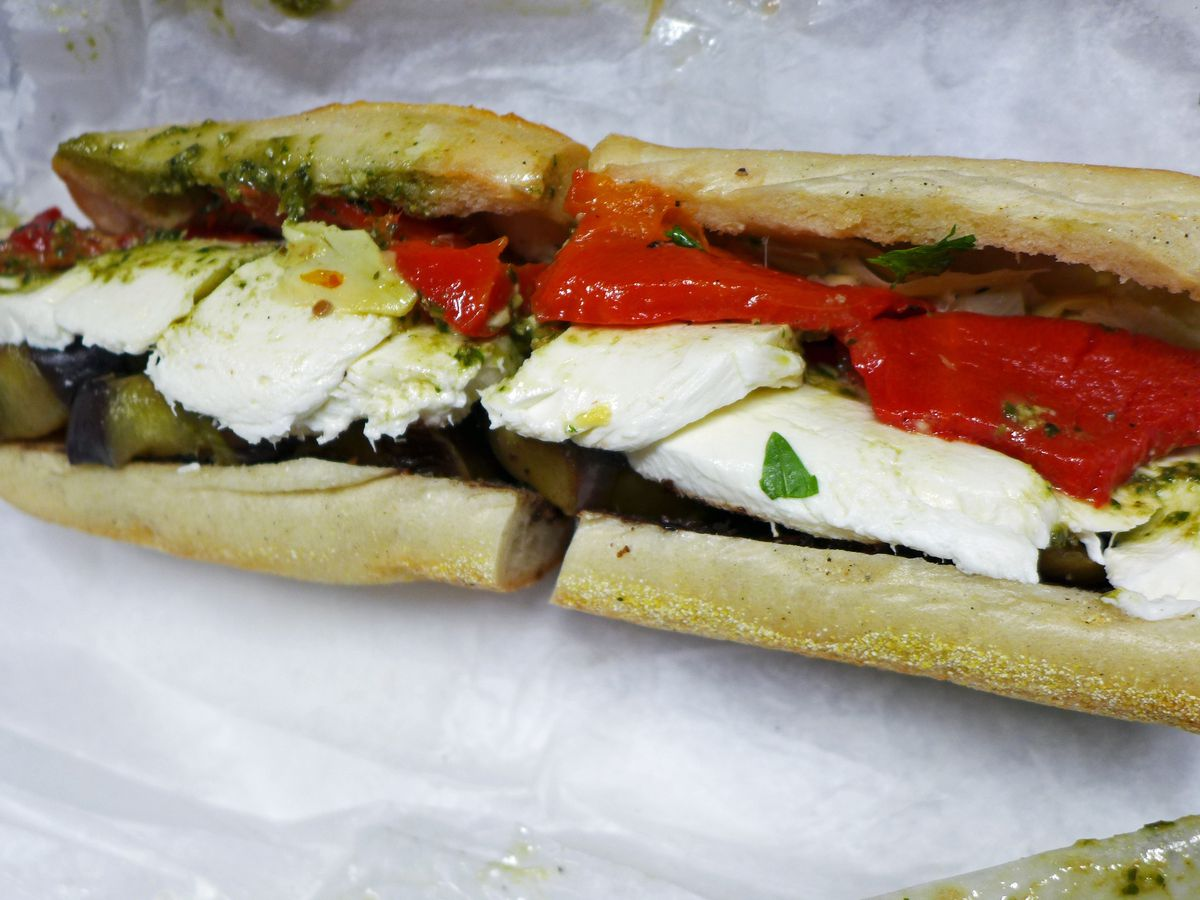 A glistening hero with white cheese and red peppers poking out.