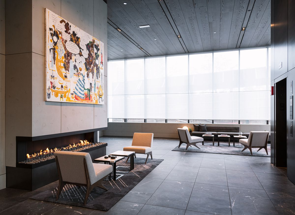 A lobby with high ceilings, stone floors, concrete walls, and a fireplace topped by contemporary art.