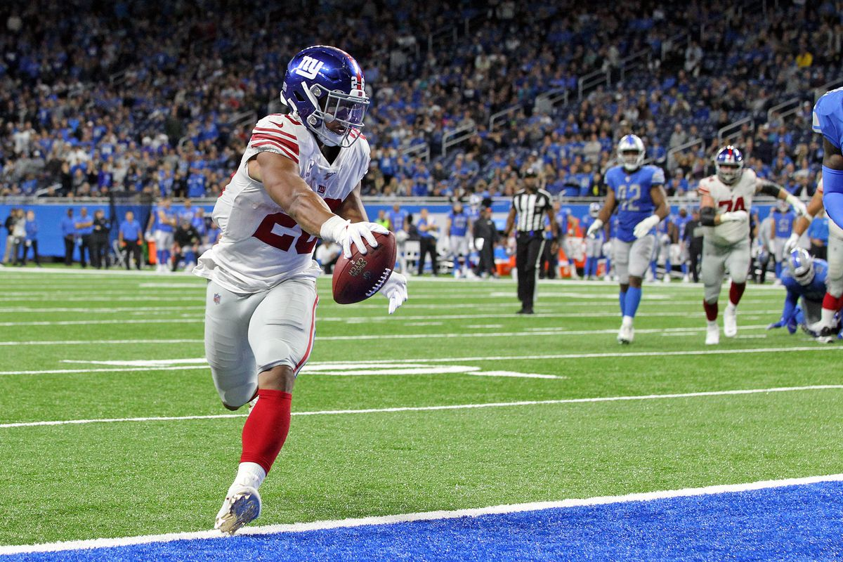 New York Giants running back Saquon Barkley (26) scores a touchdown during the second half of an NFL football game against the Detroit Lions in Detroit, Michigan.