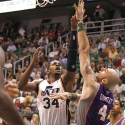 Utah's CJ Miles drives on Sun's Marcin Gortat as the Utah Jazz and the Phoenix Suns play NBA basketball Wednesday, April 4, 2012, in Salt Lake City, Utah.
