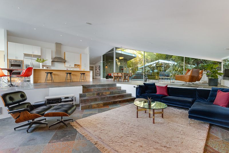 A large open room with a sunken den and stone steps leading up to a seating area and the open-concept kitchen.