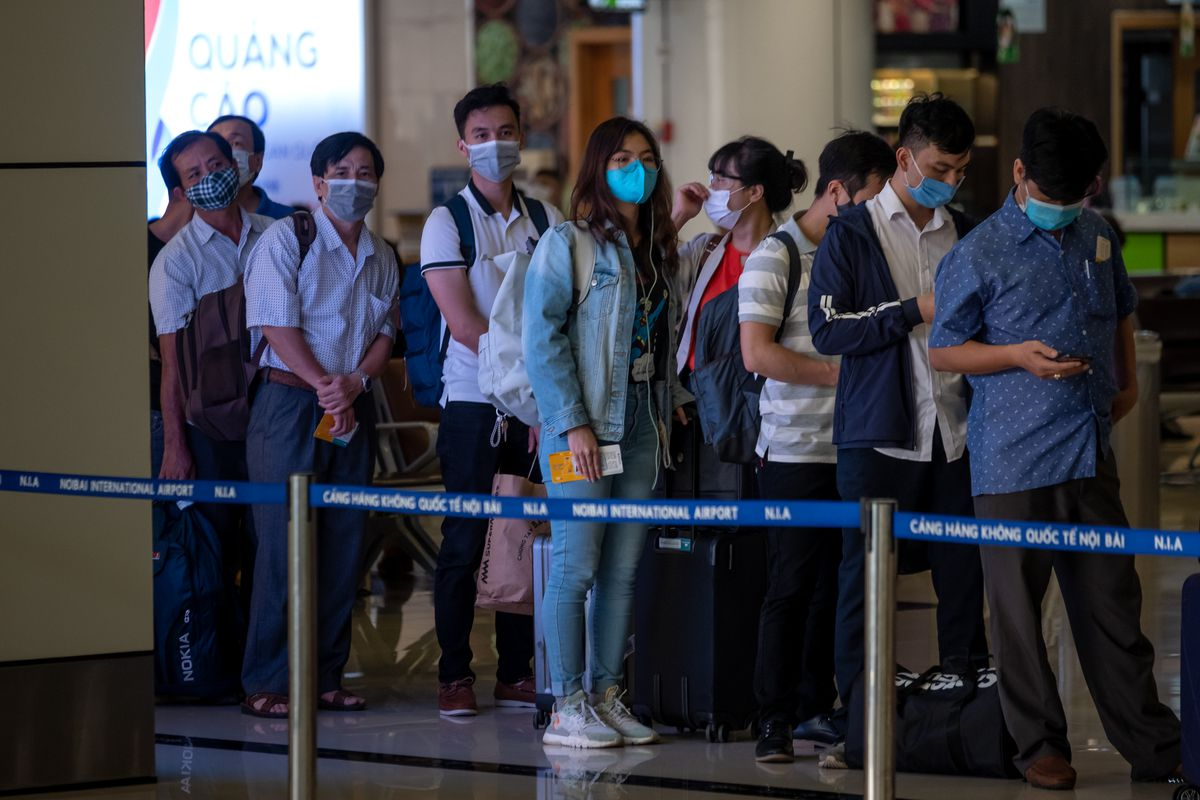 People wearing face masks board a flight at an airport in Hanoi, Vietnam.