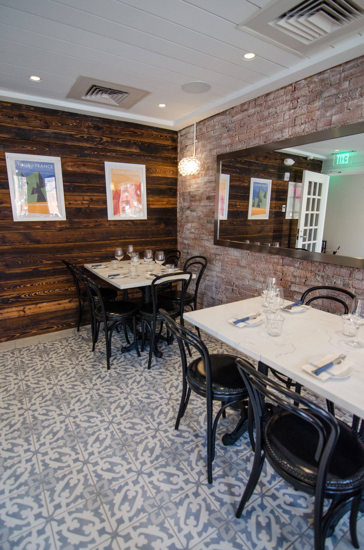 Small dining room at a restaurant with Spanish-style tiled floor, one white-washed brick wall, and one dark wood wall with a couple pieces of artwork hanging on it.