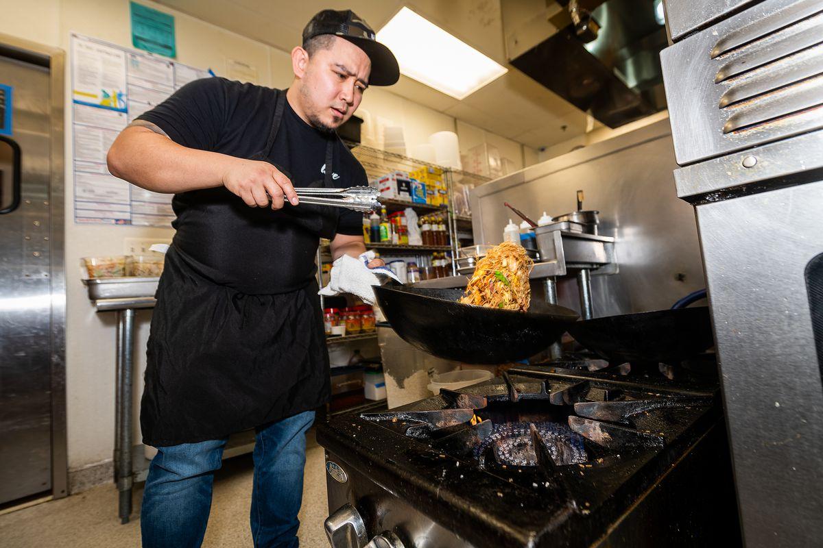 "Javier ""Ja"" Fernandez , wearing a black apron and a ballcap, tosses a wok full of pancit noodles."