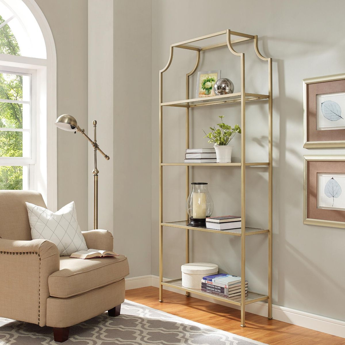 Room with beige armchair and gold-frame shelf.