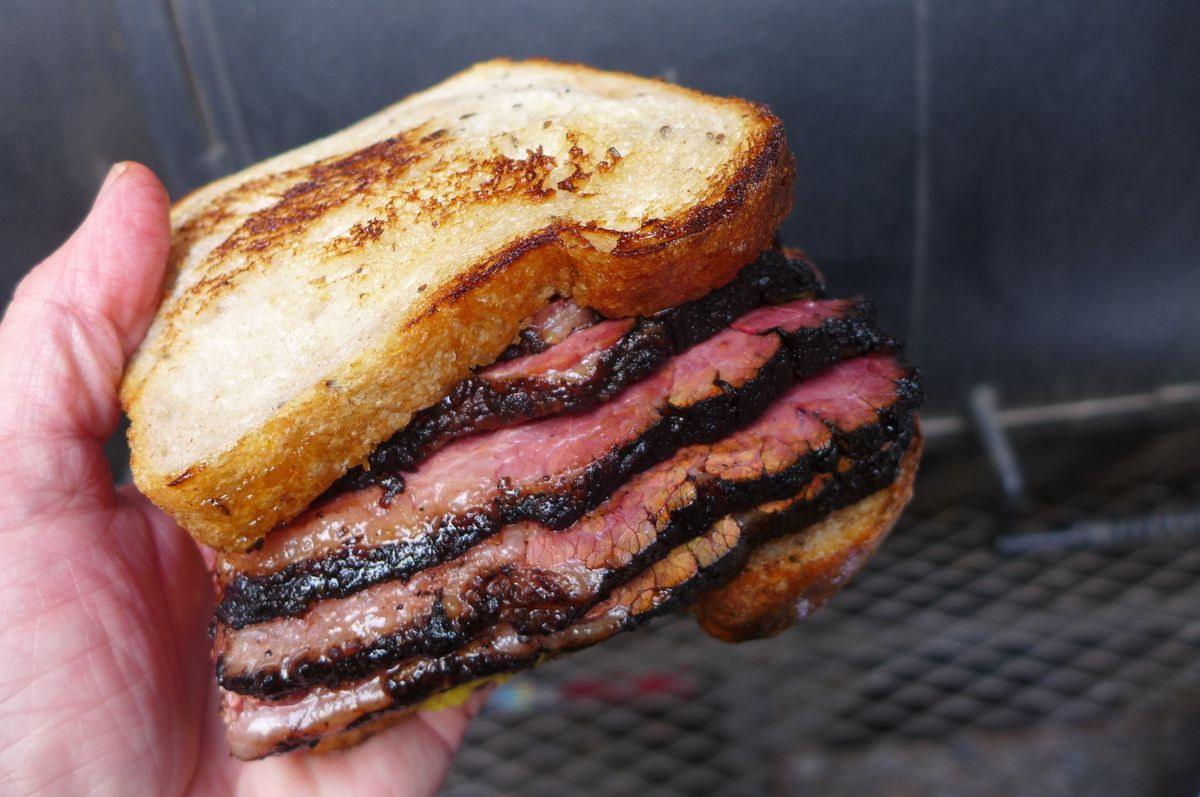 A pastrami sandwich on toasted white bread and a thick blackened spice rim.
